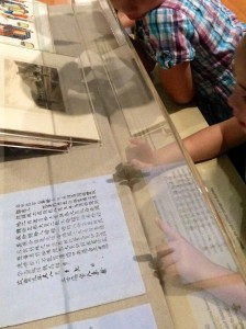 Kids examining a 19th-century Chinese labour contract, Celestial City exhibition