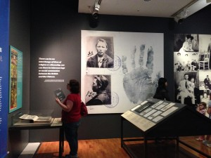Handprint and identity photographs on the wall of the Celestial City exhibition