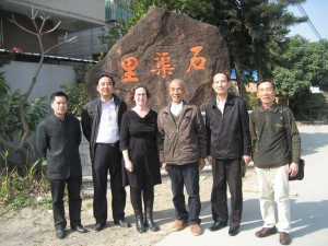 Five men and one woman in front of a large rock with the Chinese characters for Shiquli etched into it