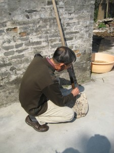 A man crouched over cleaning a shovel with a rag